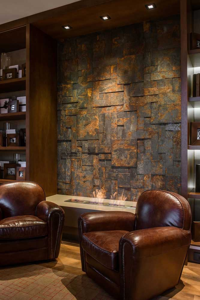 Pedra ferro na área da lareira: uma ideia incrível para decorar esse tipo de espaço; repare que a iluminação direcionada contribui para o efeito do revestimento