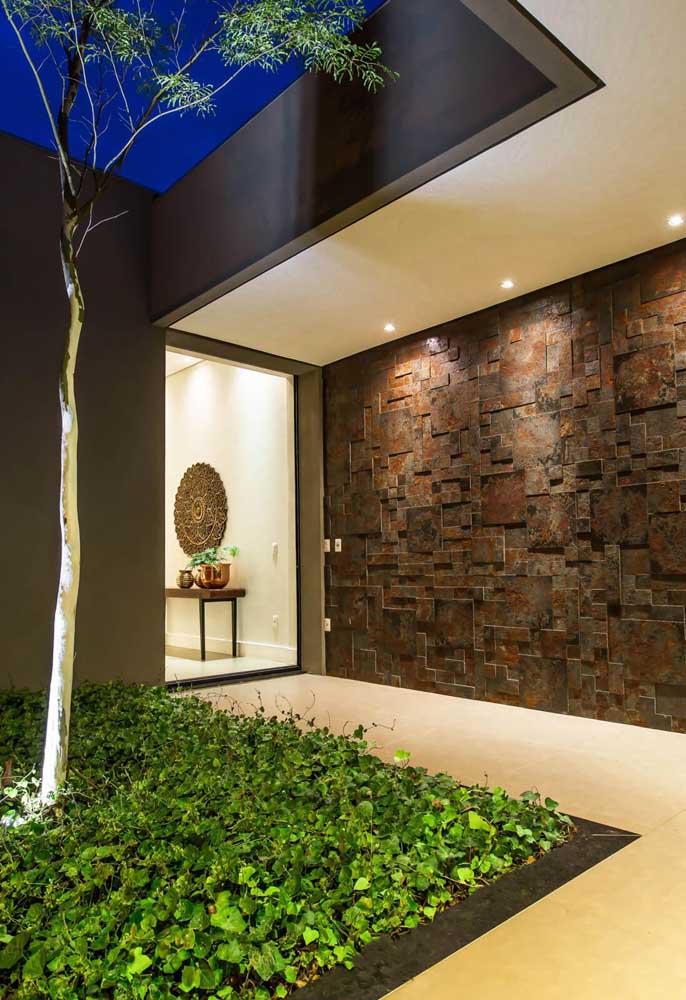 Corredor para a entrada da residência em Pedra ferro mosaico; destaque para a iluminação direcionada em spots