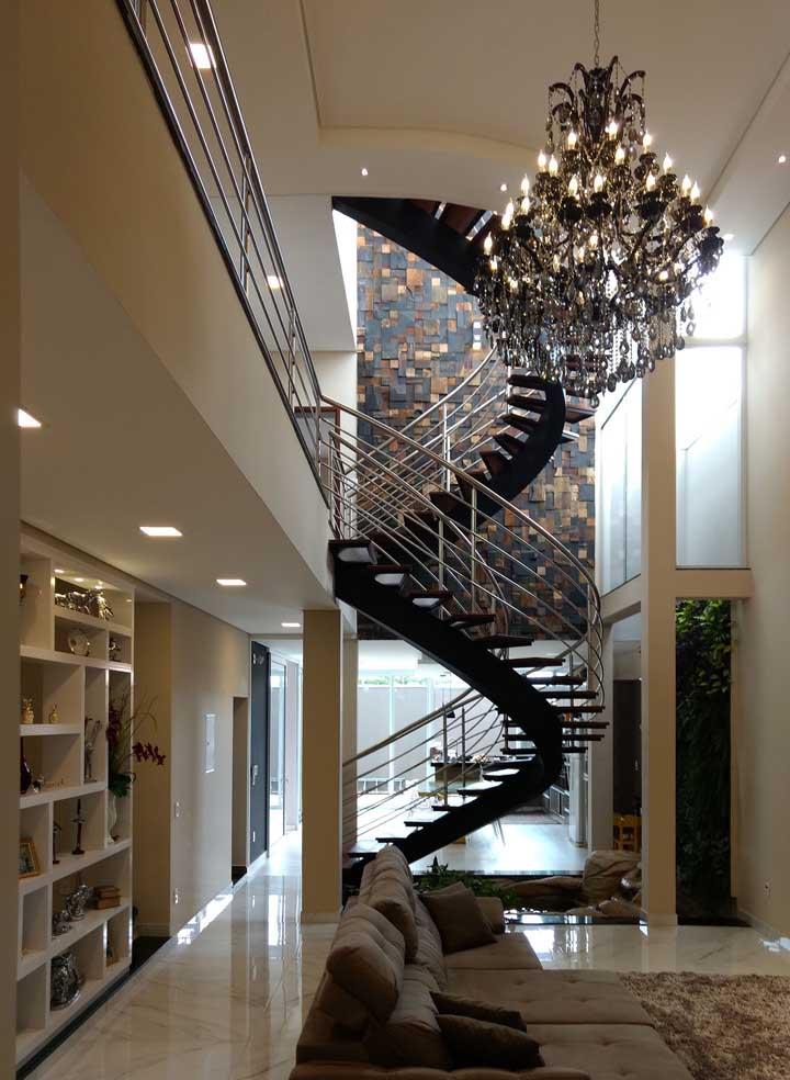 O visual diferenciado dessa escada ficou ainda mais valorizado com a parede de pedra ferro aos fundos