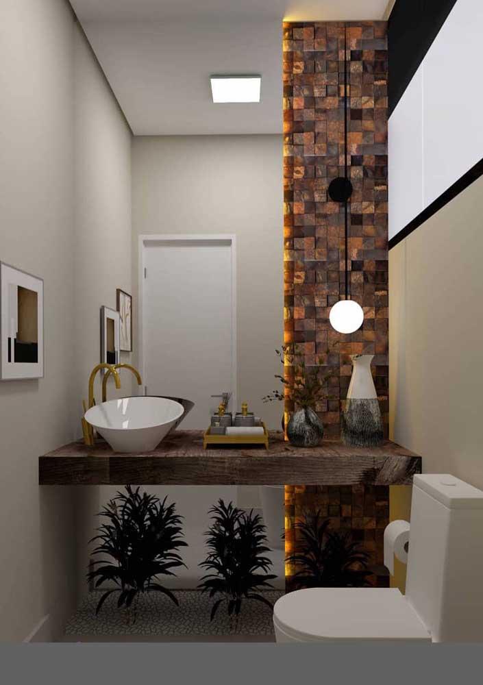 A parede em Pedra ferro deste lavabo brigou por espaço com o espelho, mas a composição acabou em um resultado lindo, combinado com a iluminação em LED atrás do espelho