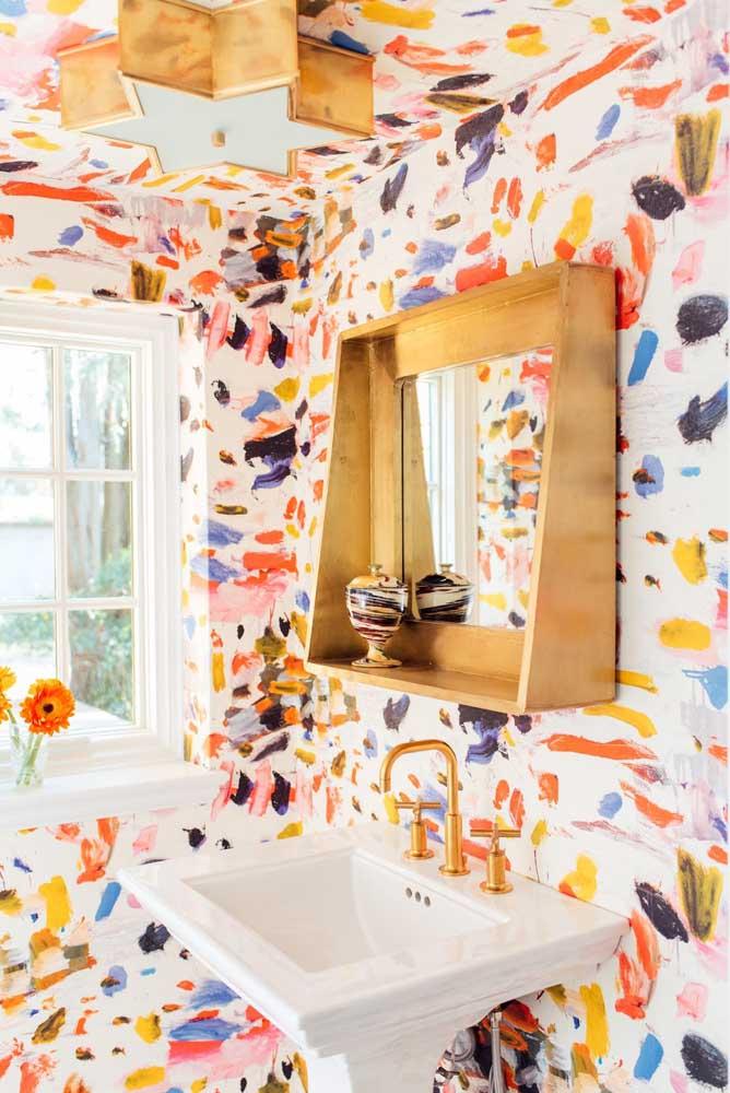 O lavabo bem iluminado contou com a alegria do papel de parede estampado com pinceladas de tinta; repare que o revestimento se estende até o teto