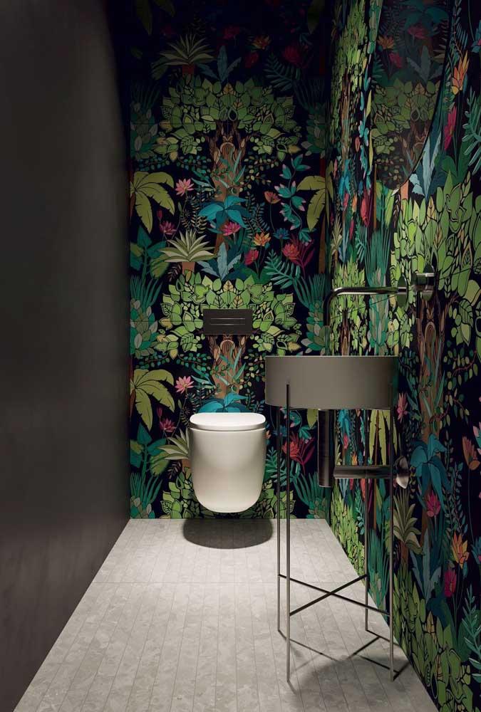 Mesmo com a ausência de iluminação natural, o lavabo investiu sem medo em um papel de parede de estampa tropical; contudo, para evitar sensação de sufocamento, uma parede neutra e lisa