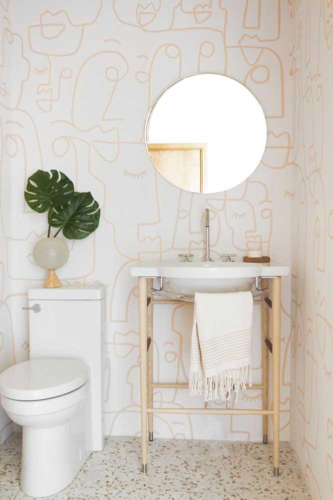 O pequeno lavabo apostou em um papel de parede claro para manter a neutralidade e iluminação
