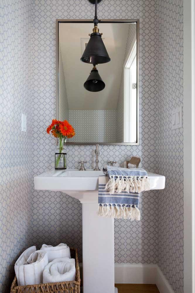 Lavabo pequeno, simples e ricamente revestido com um papel de parede neutro e delicado