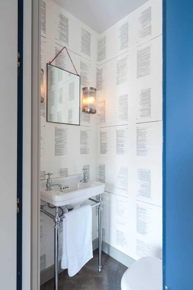 Páginas de livros estampam as paredes desse pequeno lavabo