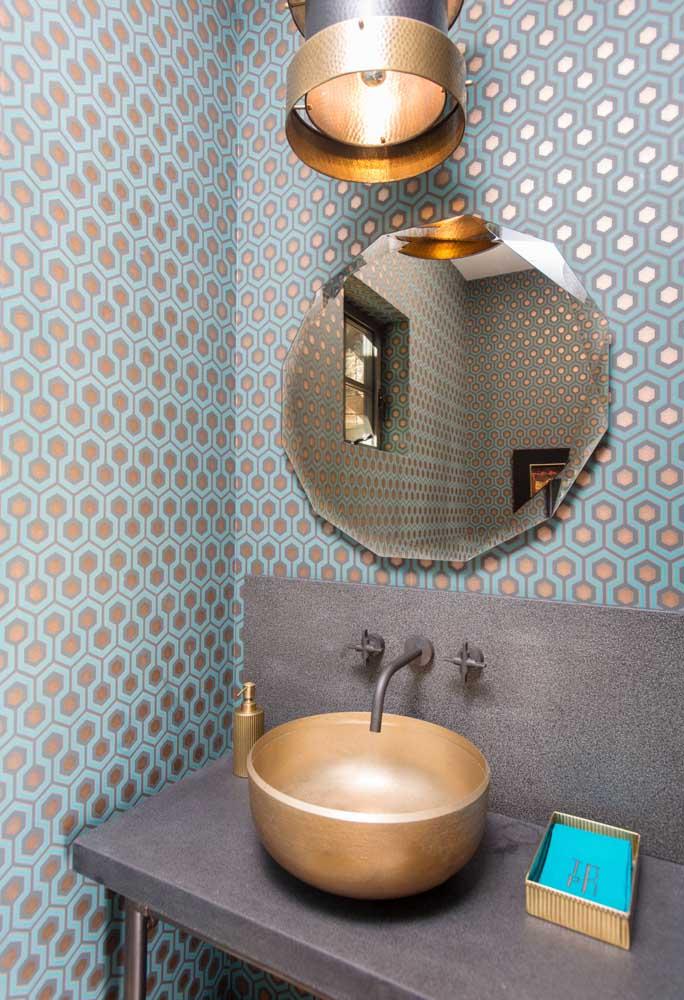 Os lindos detalhes dourados do papel de parede em perfeita harmonia com a pia e os demais detalhes do lavabo