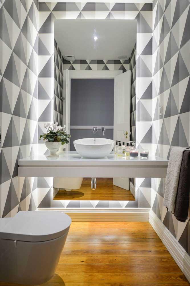 Papel de parede com estampa geométrica para o lavabo moderno; repare que o uso conjugado do espelho com a iluminação criou um efeito de amplitude incrível no espaço