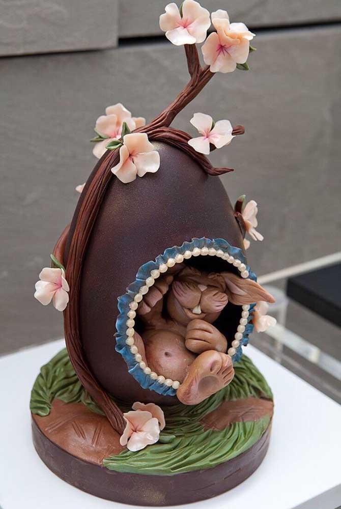 """Mais um Ovo de Páscoa para a lista de obras de arte em chocolate; aqui o estilo """"toca do coelho"""" foi conseguido com peças em chocolate ao leite e flores de açúcar"""