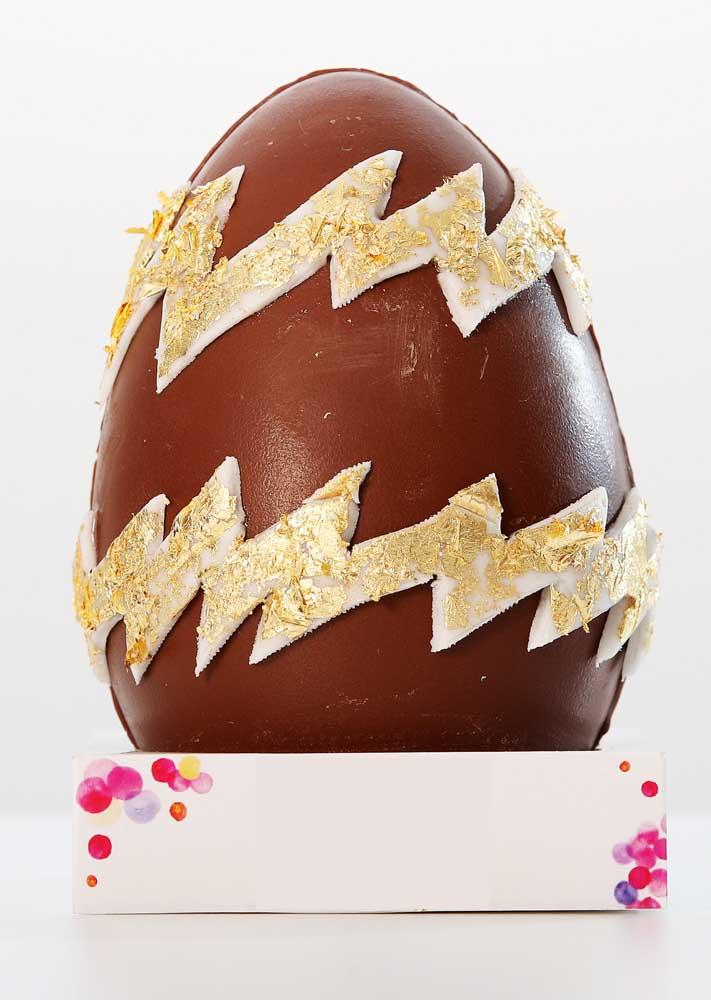 Ovo de Páscoa de chocolate ao leite simples com aplicação de detalhes em chocolate branco