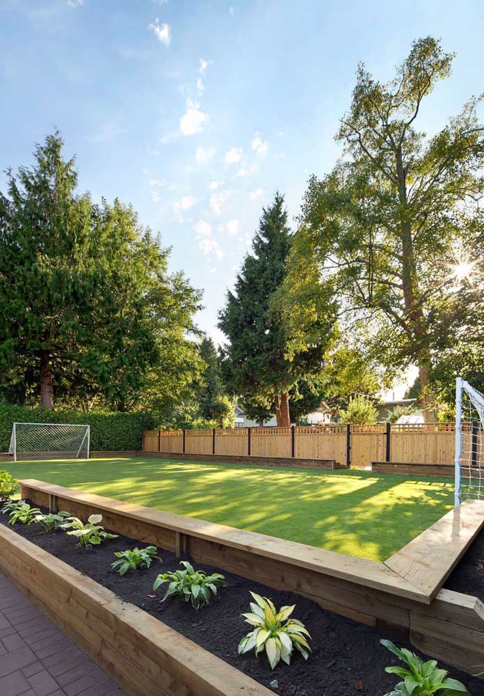 Campo de futebol forrado com a verde e macia grama bermuda