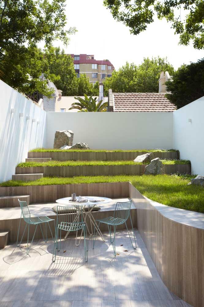Essa área externa com níveis apostou no uso da grama esmeralda para trazer cor e frescor