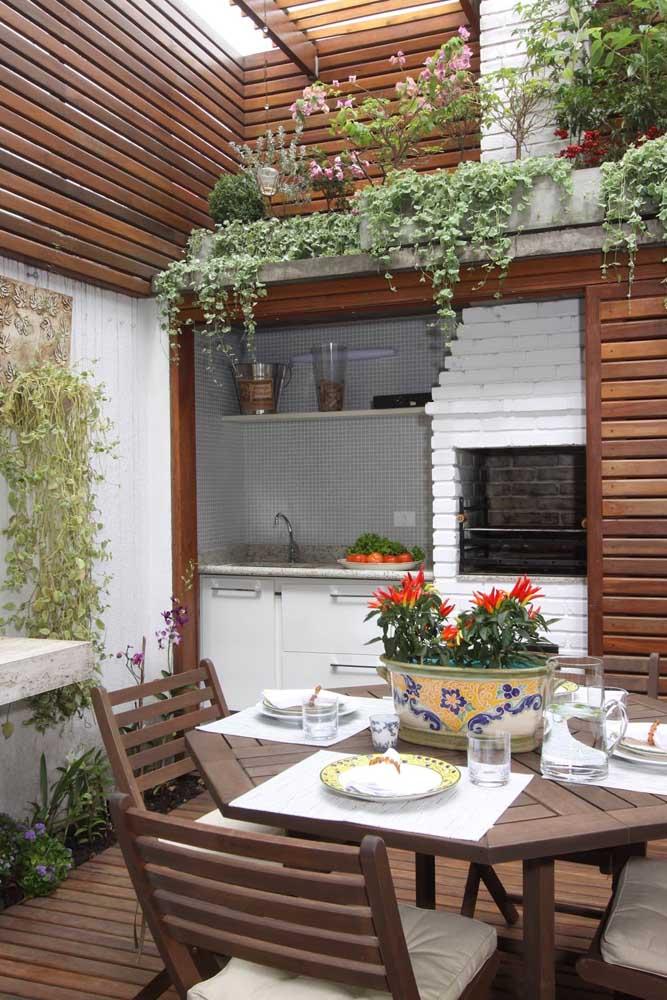 Linda referência de espaço gourmet com a churrasqueira de tijolo pintada na cor branca, combinando perfeitamente com os detalhes em madeira