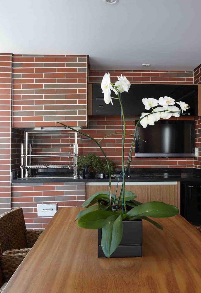 Churrasqueira de alvenaria revestida com cerâmica imitando tijolinhos; destaque para pia embutida