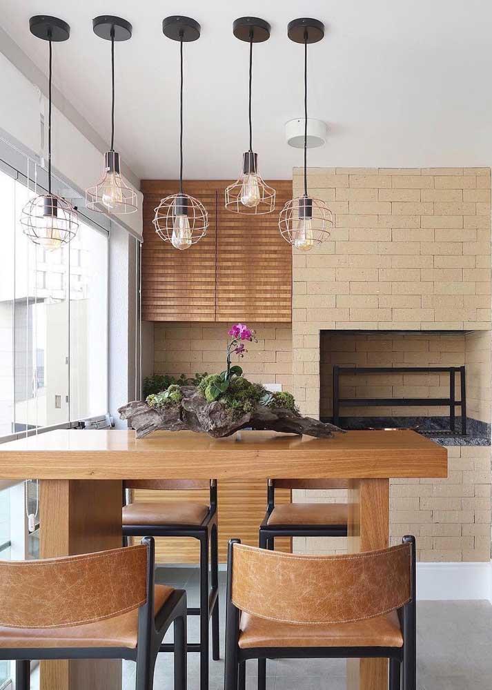 Espaço gourmet em apartamento com balcão em madeira e churrasqueira de tijolos simples