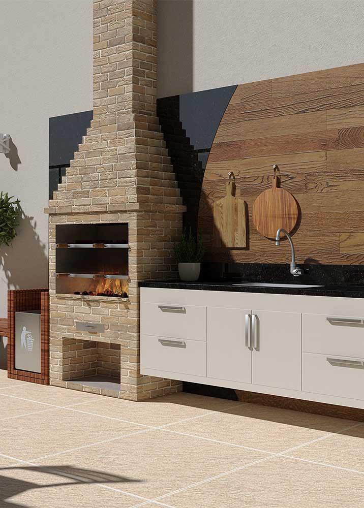 Nesse espaço gourmet, a churrasqueira de tijolo simples em modelo tradicional compartilha a atenção com o painel de madeira