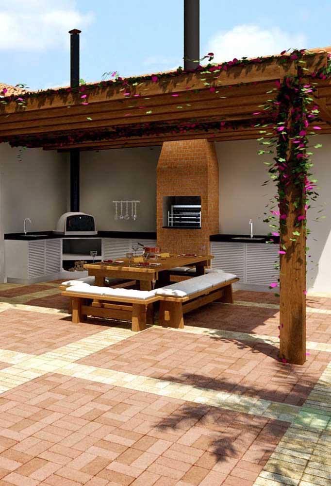 Nessa inspiração, a churrasqueira de tijolos à vista foi posicionada no centro do espaço gourmet; perceba que o espaço conta com um forno a lenha de alvenaria