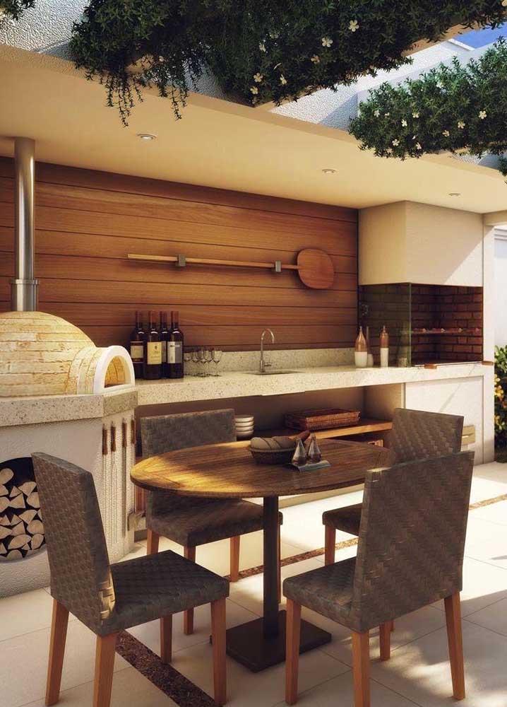 Churrasqueira em alvenaria com forno a lenha e painel de madeira ao fundo; o conjunto cria um ar acolhedor e aconchegante para o espaço gourmet