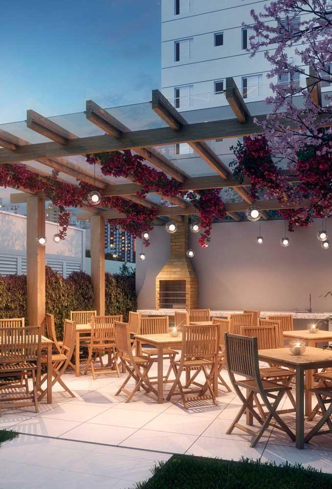 Área gourmet social com pergolado e churrasqueira de tijolo à vista