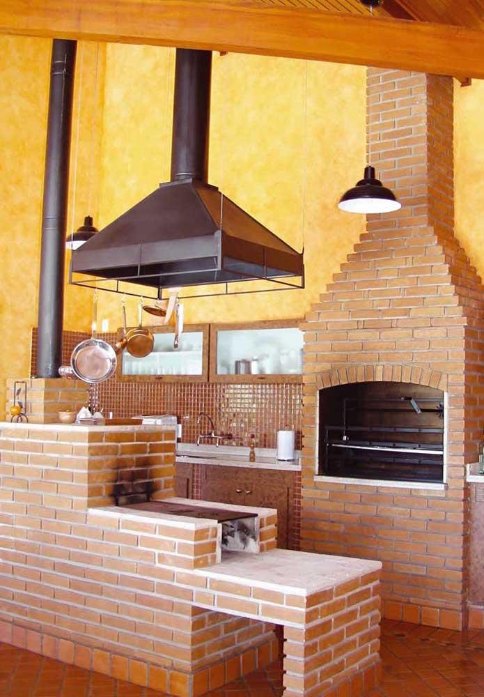 Uma área de churrasco super tradicional com churrasqueira de tijolo, forno e fogão a lenha
