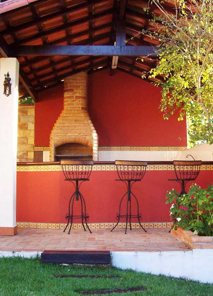 Espaço gourmet em estilo rústico com churrasqueira de tijolo aparente e chaminé com saída pelo telhado; o tom de vermelho nas paredes oferece o toque aconchegante do lugar