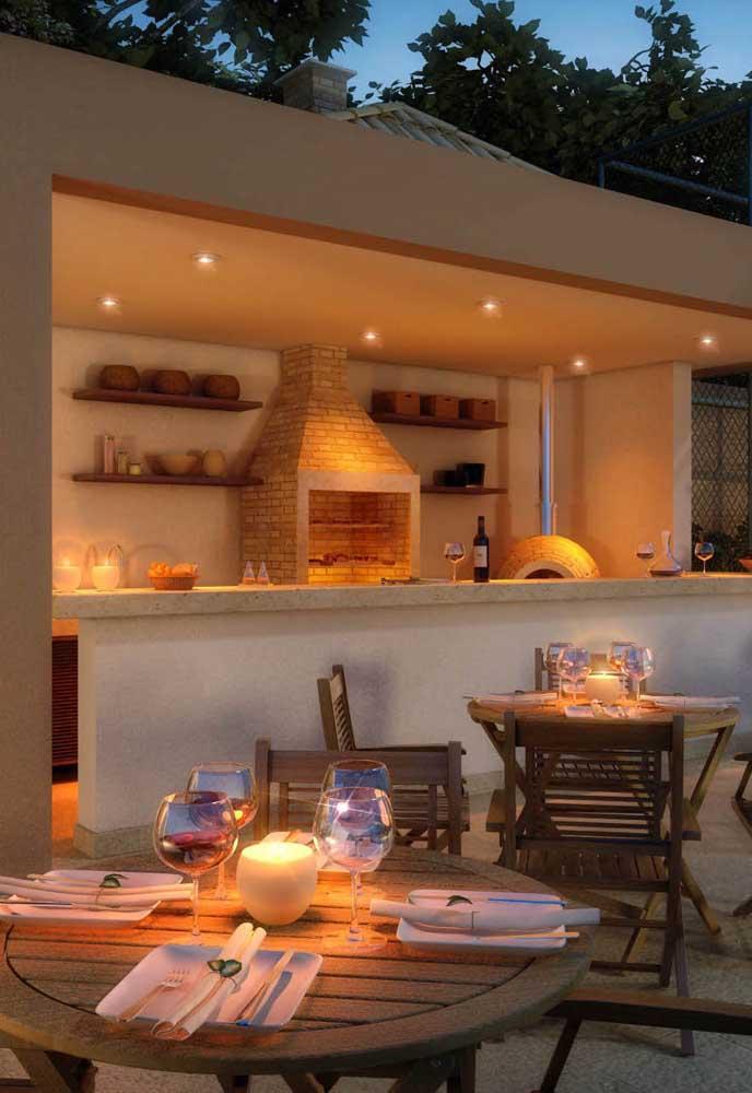 Churrasqueira de tijolos com chaminé embutida; destaque para a iluminação com spots