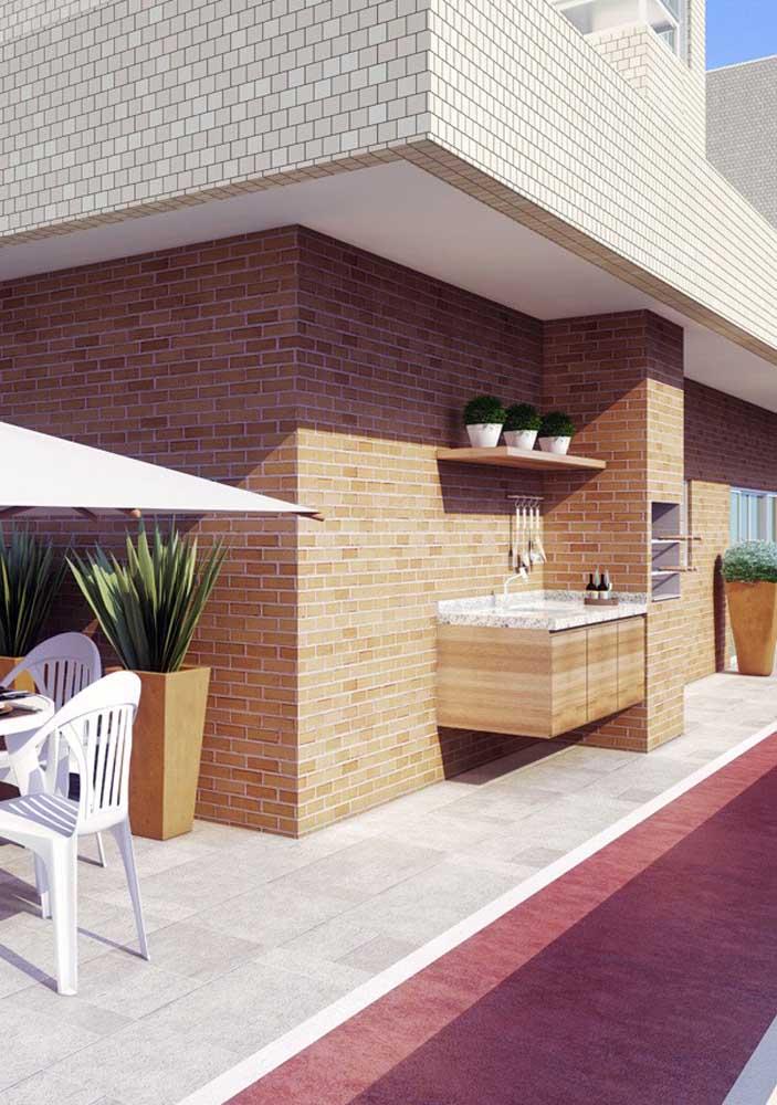 Nesse espaço gourmet aberto, a churrasqueira se apropria do revestimento de tijolos cerâmicos usado na parede