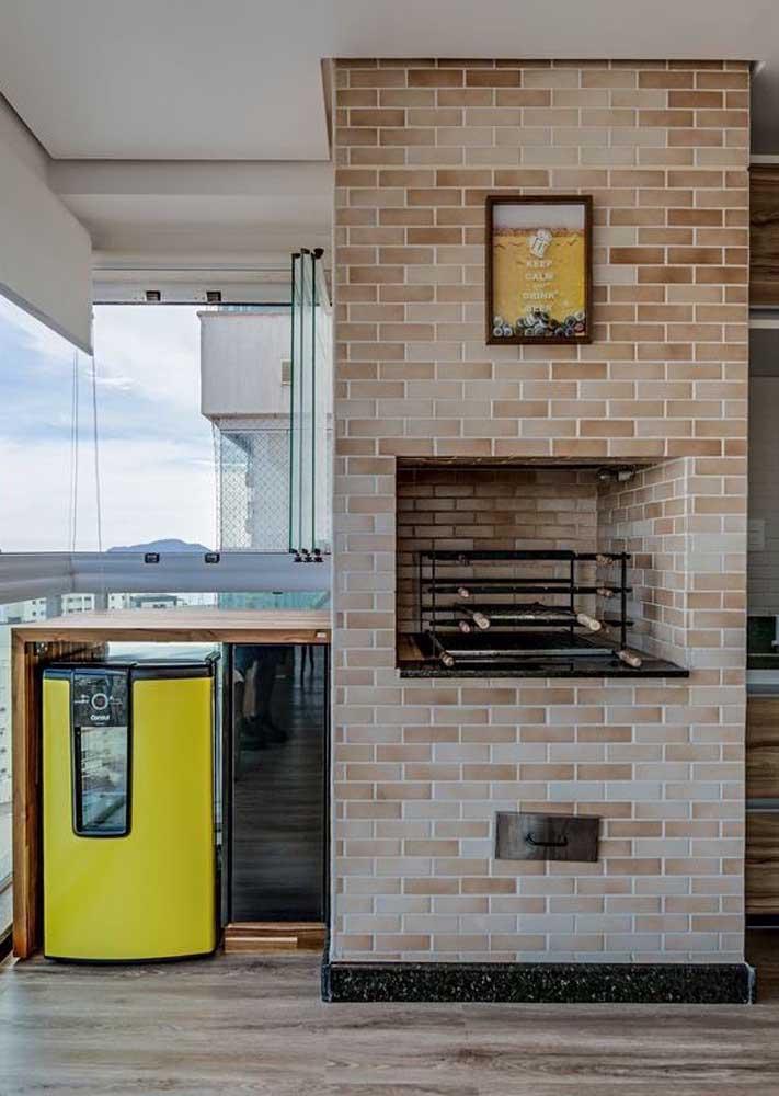 Esse terraço ganhou uma área gourmet com churrasqueira de tijolo ao lado do balcão em madeira