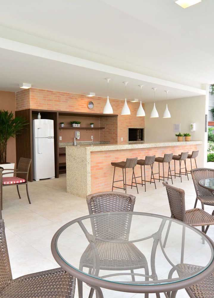 Área de churrasco ampla com balcão, mesas e churrasqueira de tijolos aparentes