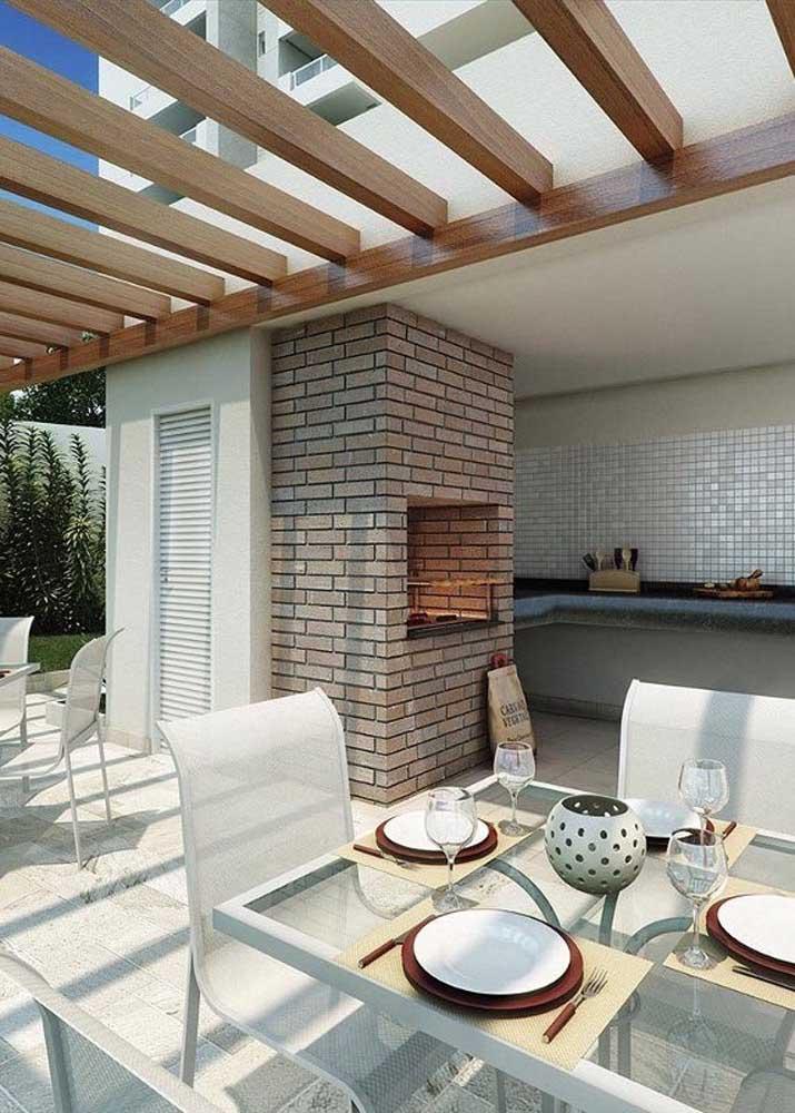Churrasqueira de tijolos para o ambiente gourmet clean e elegante com destaque para o pergolado de madeira