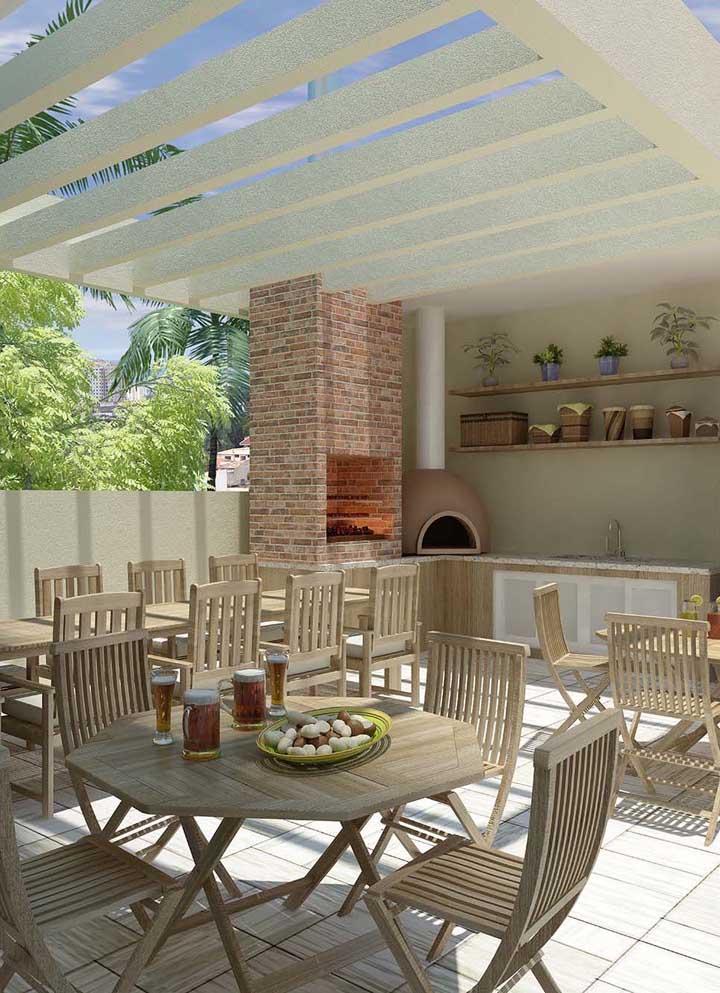 Essa área social com espaço gourmet elegante e clean conta com uma churrasqueira em tijolo e forno a lenha