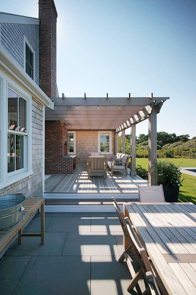 Churrasqueira de tijolo à vista virada para área aberta da casa com cobertura de pergolado