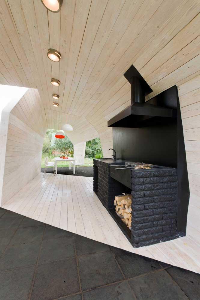 Espaço moderno com churrasqueira de tijolos pintados na cor preta, ideal para ambientes em estilo moderno e industrial