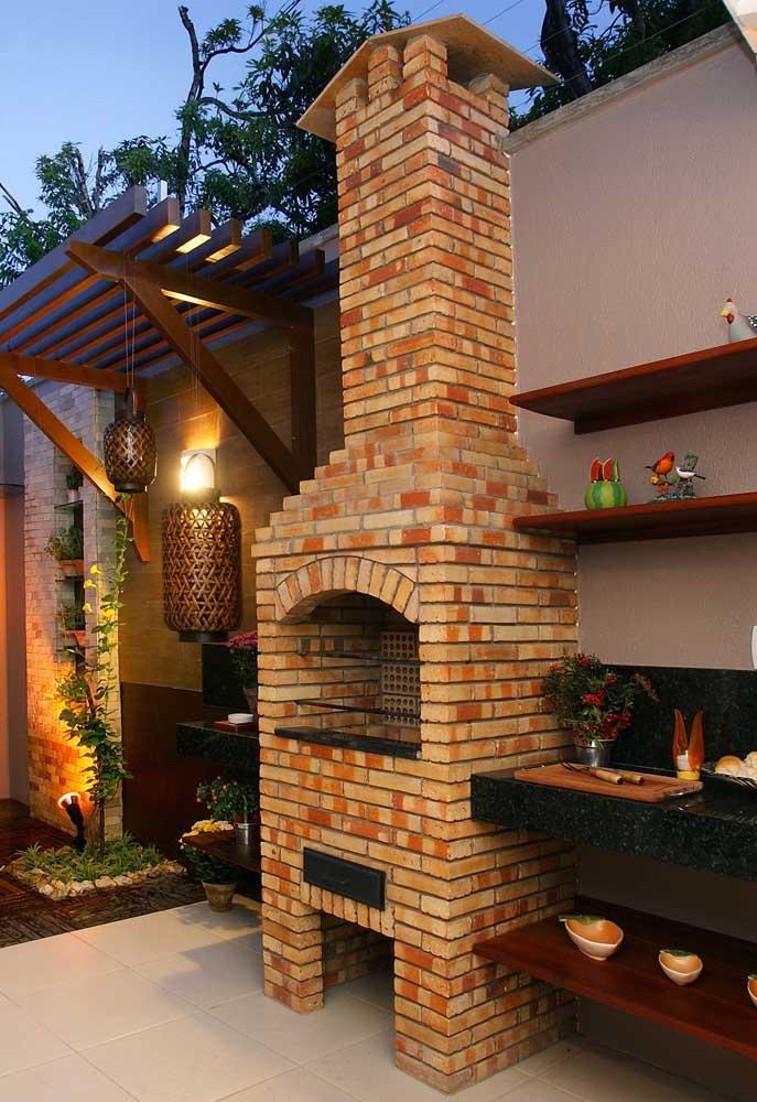 Churrasqueira de tijolos aparentes em espaço aberto; as prateleiras ao lado da churrasqueira são um charme extra no local