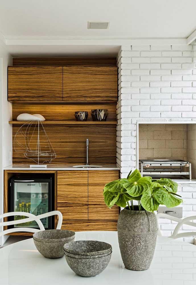 A varanda deste apartamento ganhou um espaço gourmet belíssimo com churrasqueira de tijolos pintados em branco