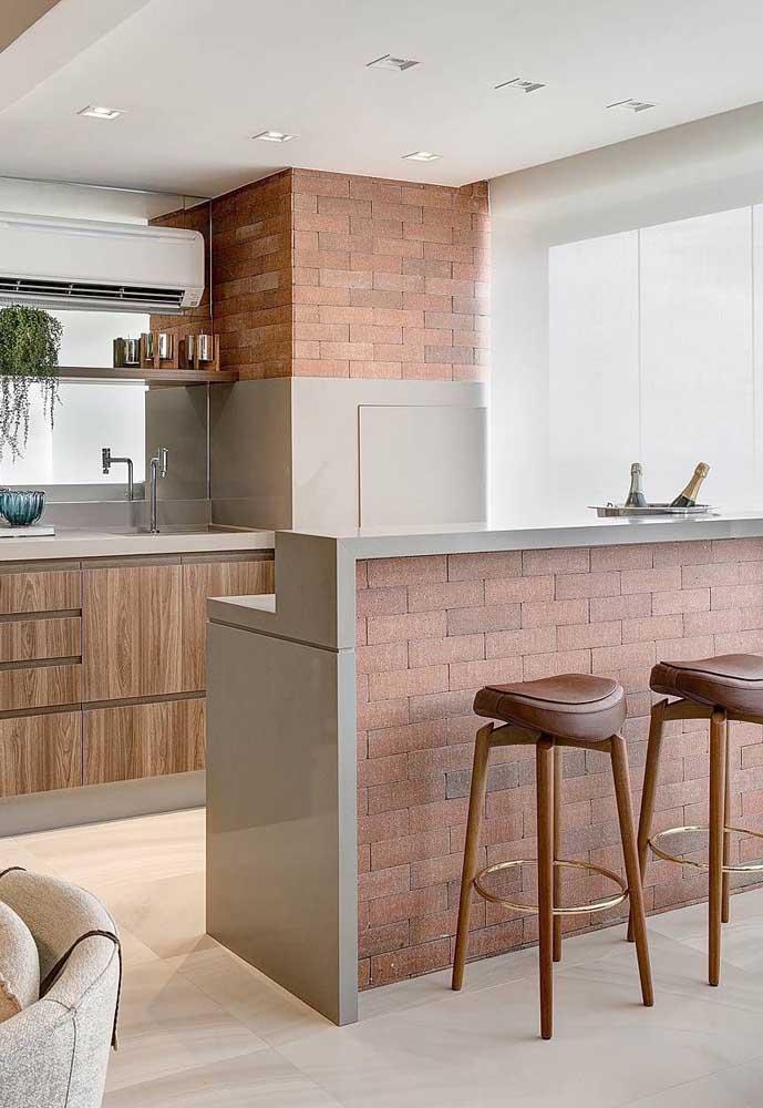 O espaço gourmet ficou moderno e sofisticado com a escolha de um tipo diferenciado de tijolos para a churrasqueira, detalhe que eles também foram aplicados no balcão