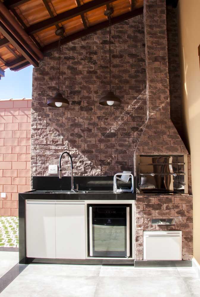 Churrasqueira de tijolo em área coberta com pia e frigobar; repare que o mesmo tijolo usado na churrasqueira também reveste a parede