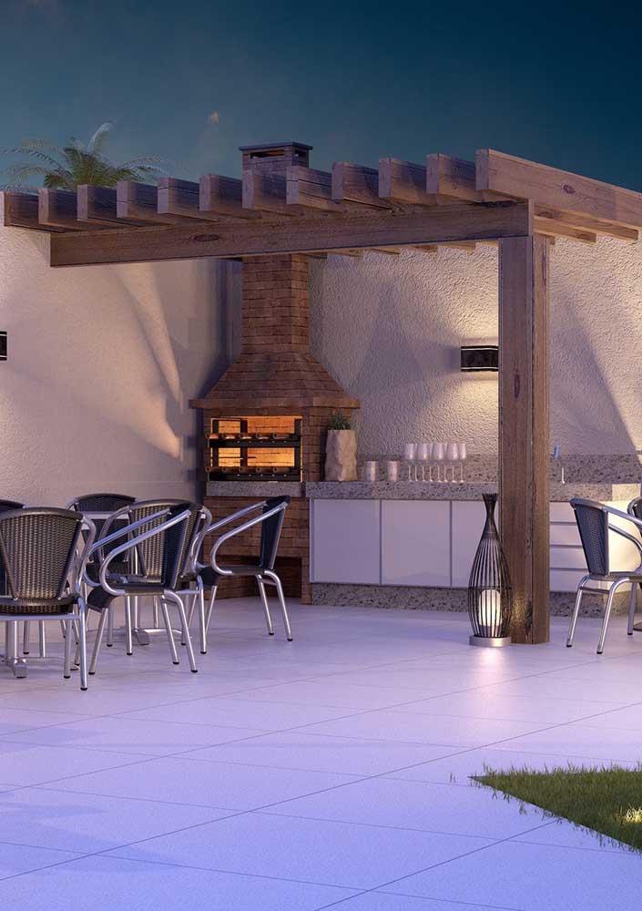 A área externa dessa casa ganhou um espaço para a churrasqueira de tijolo com pia em granito e cobertura em pergolado