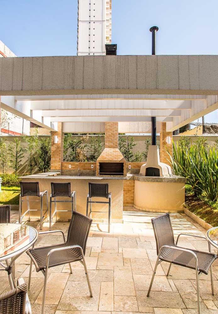 Espaço gourmet amplo e espaçoso com churrasqueira de tijolo, forno a lenha e balcão em alvenaria com banquetas