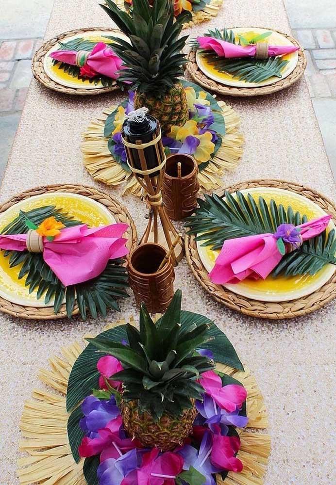 Mesa ricamente decorada no tema luau; plantas tropicais, frutas e cordões de flores são alguns dos destaques