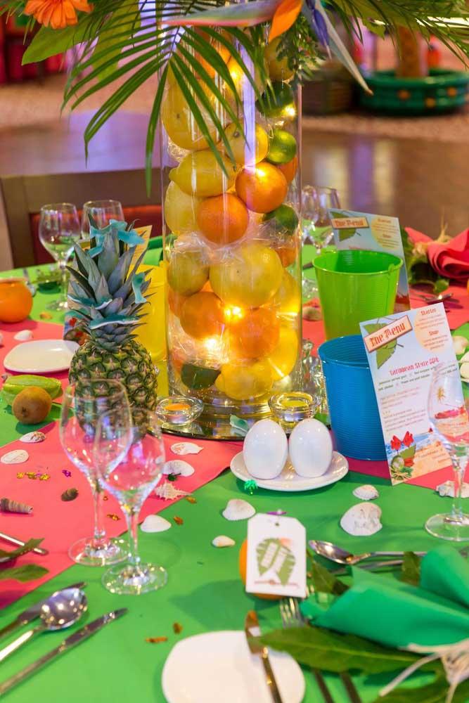 Linda essa decoração de festa luau: a ideia aqui foi usar um recipiente de vidro preenchido com frutas e luzes