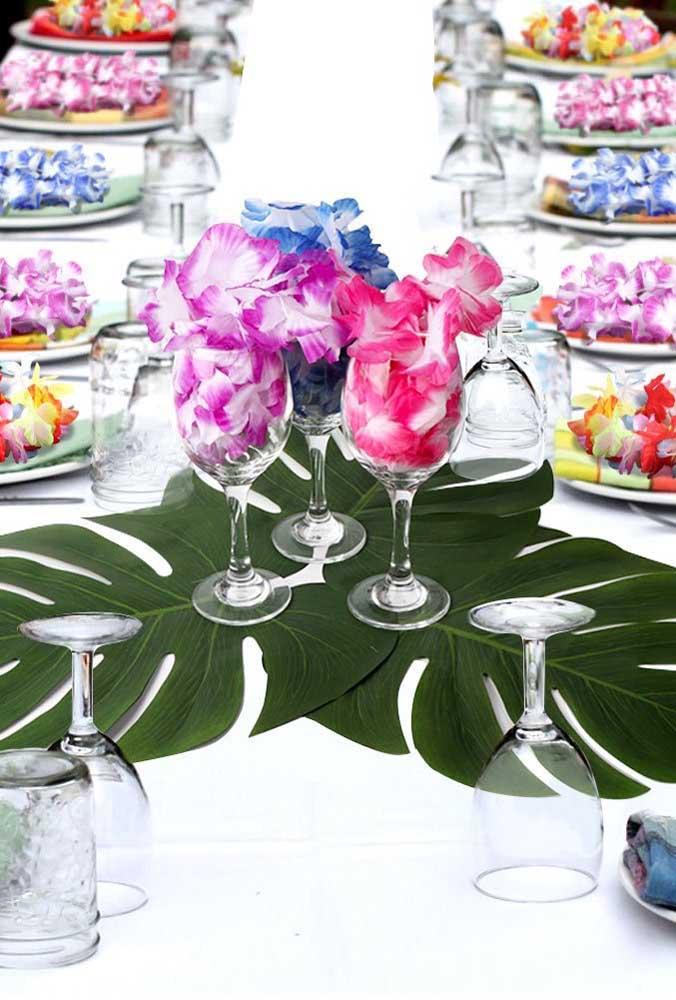 Nessa mesa, as folhas da costela de adão são a atração principal; as pétalas de flores completam o cenário