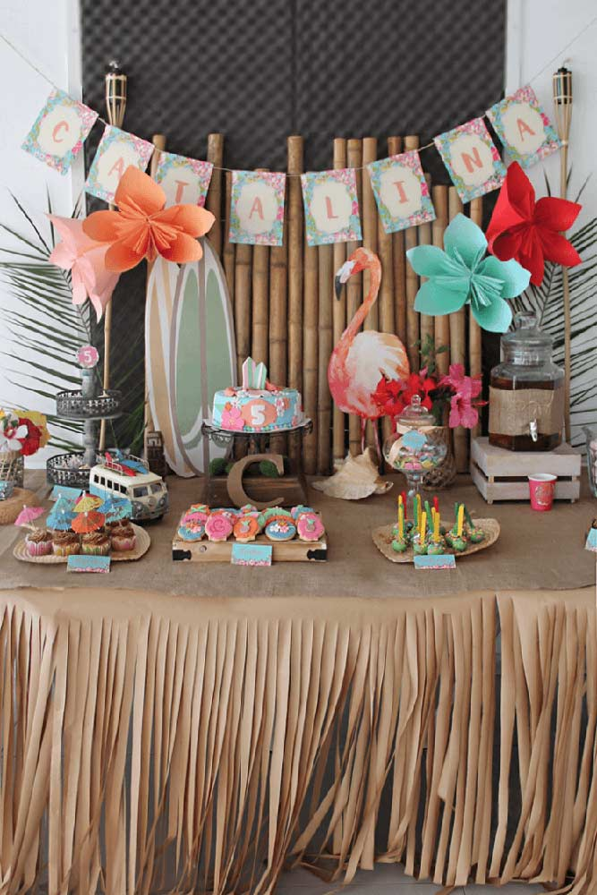 Festa de aniversário infantil com o tema luau; a mesa do bolo foi decorada com papel kraft e um painel rústico de bambu