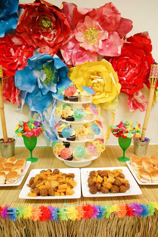 Aqui nessa festa luau são as flores de papel e os guarda chuvinhas para cupcakes que chamam a atenção; para comer, salgadinhos variados