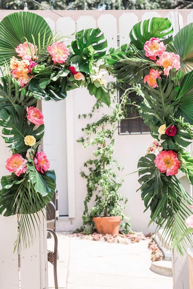 Plantas e flores tropicais formam um arco lindo arco na entrada da festa luau
