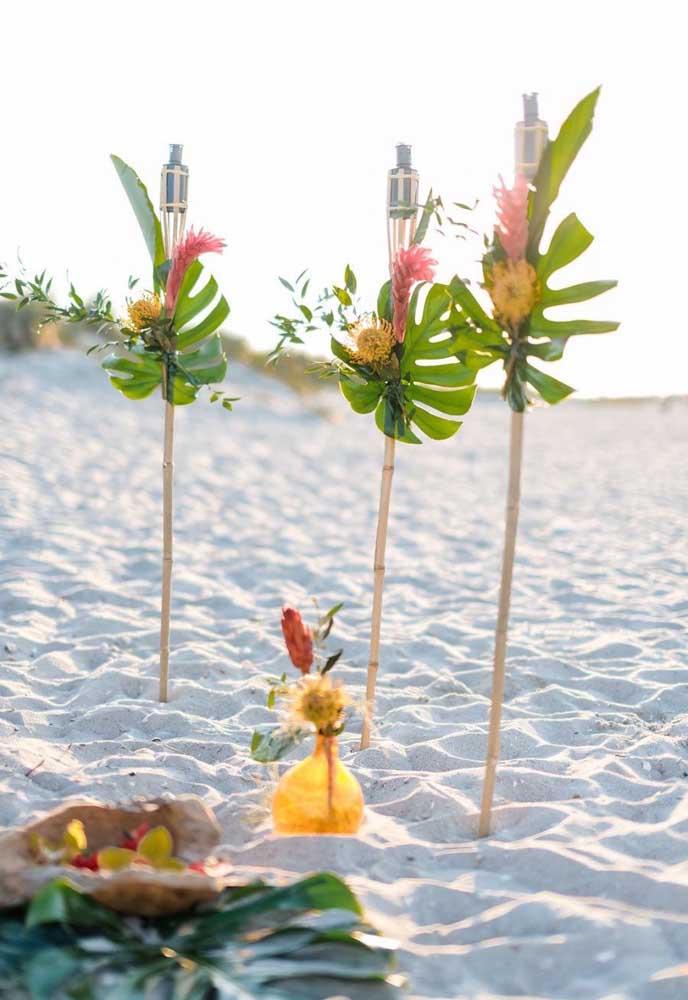 Esse luau pé na areia conta com tochas para iluminar a noite que se aproxima