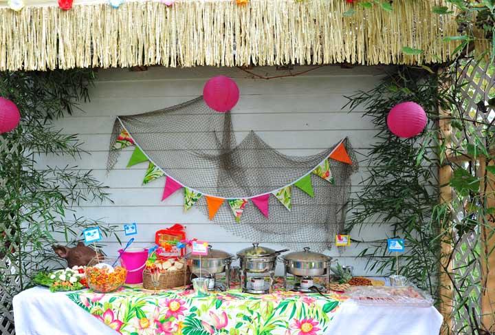 Já nessa outra festa luau, a rede de pesca virou painel da mesa de bolo