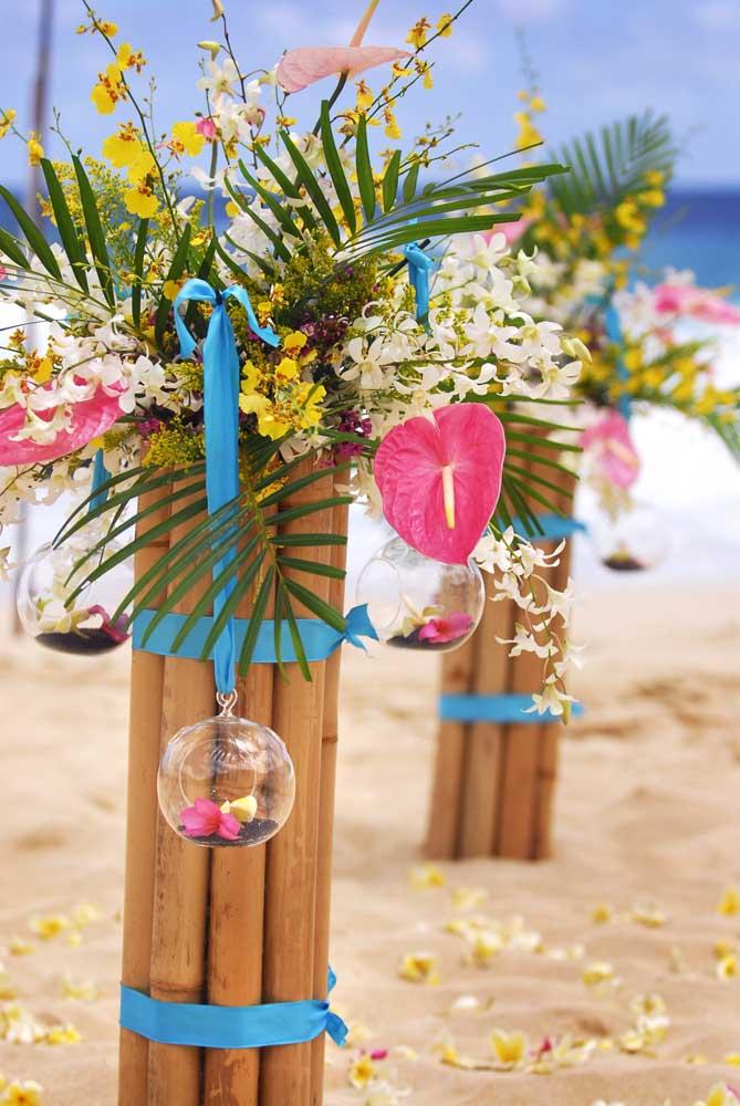 Casamento na praia com tema luau; o caminho para o altar foi decorado com suportes de bambu e flores tropicais