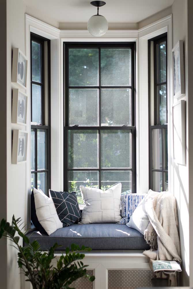 Bay Window com moldura preta; o sofá aconchegante com manta e almofadas é um convite para um chá e uma boa leitura