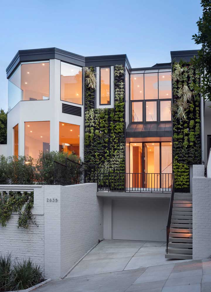Nessa fachada de sobrado, a Bay Window divide a atenção com o jardim vertical