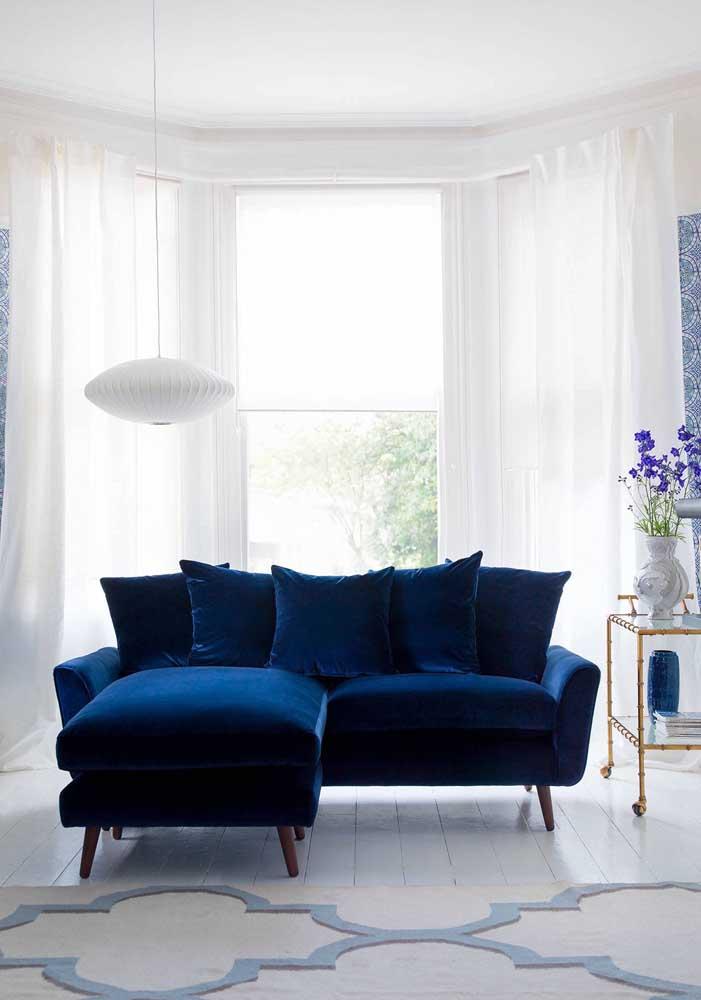 Já aqui, o sofá de veludo azul contraste lindamente com a Bay Window branca aos fundos